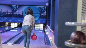 Женщина в клубе для боулинга бросает шарик видеоматериал
