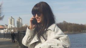 Девушка имеет потеху говоря на телефоне видеоматериал