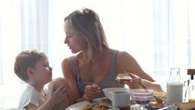 Девушка имея завтрак и целуя его сына акции видеоматериалы