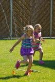 Девушка имея потеху с спринклером в саде Стоковая Фотография