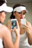Девушка имея потеху с телефоном перед зеркалом стоковые фото