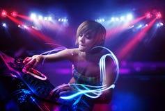 Девушка диск-жокея играя музыку с светлыми фокусировками коротких волн на этапе стоковое изображение