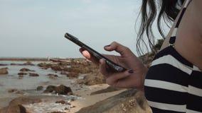 Девушка использует мобильный телефон на пляже на предпосылке моря и камней пишет сообщение видеоматериал