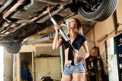 Девушка использует drainer масла для поднятого автомобиля стоковая фотография rf