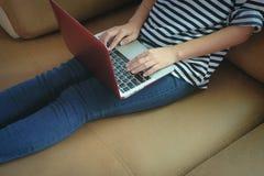 Девушка используя компьтер-книжку компьютера на софе Стоковое Изображение RF