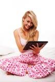 Девушка используя таблетку на ее кровати Стоковое Изображение
