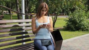 Девушка используя smartphone в парке города женщина сидя на стенде с устройствами в парке сток-видео