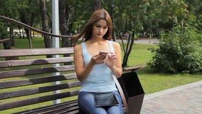 Девушка используя smartphone в парке города женщина сидя на стенде с устройствами в парке видеоматериал