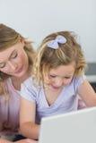 Девушка используя компьтер-книжку с матерью Стоковое фото RF