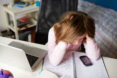 Девушка используя мобильный телефон вместо изучать в спальне