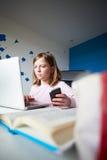 Девушка используя мобильный телефон вместо изучать в спальне стоковое изображение rf