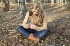 Девушка используя радиотелеграф интернета на smartphone в natu Стоковое фото RF