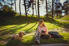 Девушка используя таблетку в парке с собакой Стоковые Фотографии RF