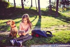 Девушка используя таблетку в парке с собакой Стоковые Изображения