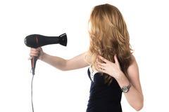 Девушка используя фен для волос стоковые фото