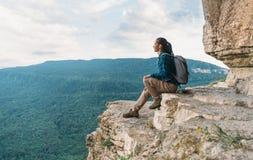Девушка исследователя сидя на скале Стоковое Фото
