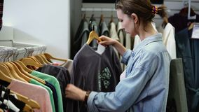 Девушка ищет совершенная одежда на вешалках на строке в гипермаркете Выбирать чего купить Cocept покупок видеоматериал