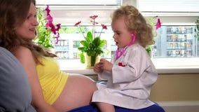 Девушка и беременная дочери будут матерью женщины играя доктора с стетоскопом видеоматериал