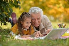 Девушка и дед с компьтер-книжкой Стоковые Изображения RF