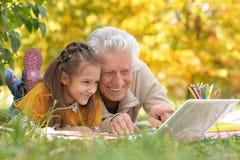Девушка и дед с компьтер-книжкой Стоковая Фотография RF