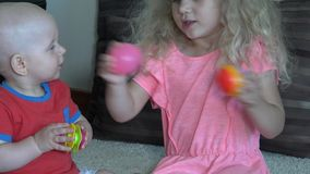Девушка и ее мальчик маленького брата играя с красочными шариками дома видеоматериал