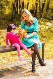 Девушка и ее мать играя outdoors с осенними кленовыми листами Ребёнок выбирая золотые листья Стоковое Фото