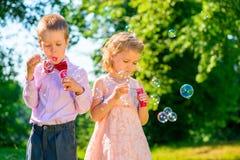 Девушка и ее друг с пузырями мыла Стоковая Фотография RF