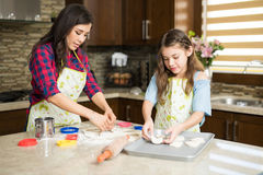 Девушка и ее тесто печенья вырезывания мамы Стоковые Изображения RF