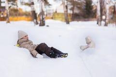Девушка идет в древесины в зиме Она лежала в снеге с плюшевым медвежонком фаворита игрушки Счастливый Стоковая Фотография