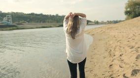 Девушка идет на воду вдоль берега и смотреть сток-видео