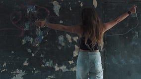 Девушка идет на подземный проход и слушает к музыке от smartphone Девушка в наушниках и вскользь одеждах акции видеоматериалы