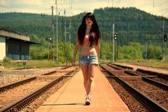 Девушка идет на рельсы на заходе солнца Стоковая Фотография