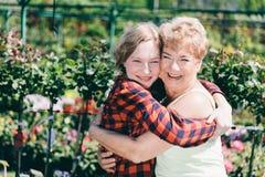 Девушка и женщина обнимая один другого в саде Стоковая Фотография