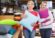 Девушка и зрелые клиенты женщины показывая купленные подушки Стоковая Фотография