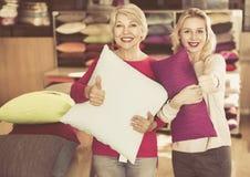 Девушка и зрелые клиенты женщины показывая купленные подушки Стоковое Фото