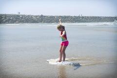 Девушка или предназначенный для подростков учить ехать skimboard на побережье Орегона стоковое фото