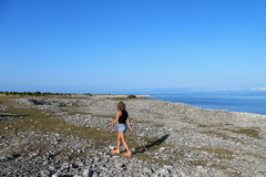 Девушка и каменистый пляж Стоковые Изображения