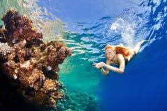 Девушка и кораллы в море стоковая фотография rf