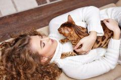 Девушка и кот лежа на софе hugs Стоковое фото RF