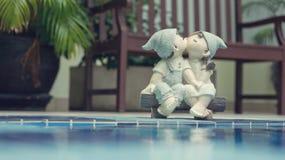 Девушка и куклы мальчика, целуя и сидя около бассейна Стоковые Фотографии RF