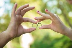 Девушка и мальчик держат кольцо в их руках на зеленой предпосылке любовная история девушки сада мальчика целуя Стоковое Изображение RF