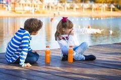 Девушка и мальчик играя на пляже на времени захода солнца стоковые изображения
