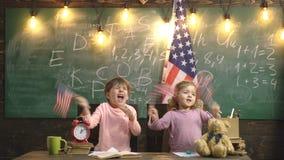 Девушка и мальчик развевая американские флаги на школе Концепция Дня независимости Счастливая прелестная маленькая белокурая кавк акции видеоматериалы