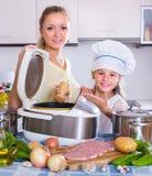 Девушка и мама варя с multicooker Стоковые Фото