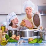 Девушка и мама варя с multicooker Стоковые Изображения RF