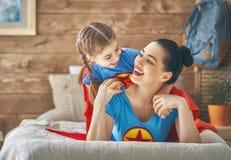 Девушка и мама в костюме супергероя Стоковые Изображения