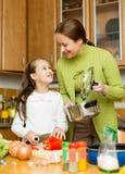 Девушка и мать делая суп Стоковые Изображения