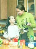 Девушка и мать делая суп Стоковая Фотография RF