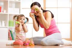 Девушка и мать ребенк имеют потеху с игрушками головоломки Малыш молодой женщины и ребенка сидя на поле и играть воспитательный стоковые изображения