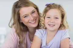 Девушка и мать усмехаясь совместно дома Стоковое фото RF